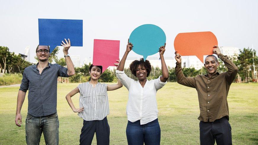 Vier verschiedene Menschen halten Sprechblasen in die Luft