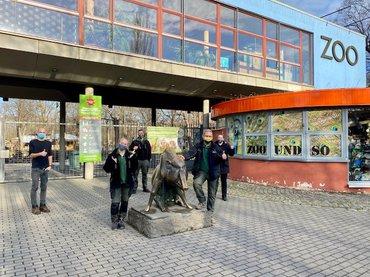 Mitglieder zeigen stolz Tarifergebnis in die Kamera vor dem Eingang des Zoos Dresden